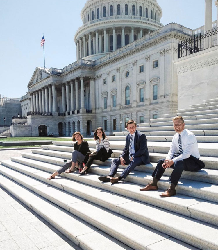 Students wearing professional clothing sitting on the steps of the capital